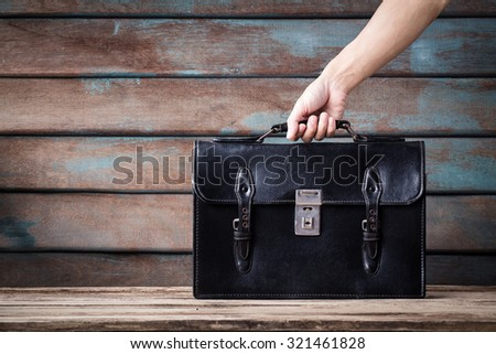 vintage classic of hand man holding leather Schoolbag on wooden background. - stock photo