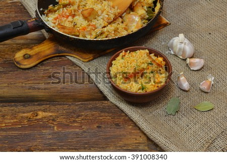 Vintage clay bowl with traditional spicy food pilaf, frying pan with pilaf on wooden background and the burlap. Pilaf with meat  - stock photo