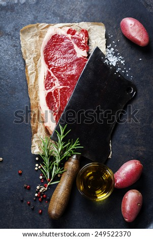 vintage cleaver and raw beef steak on dark background - stock photo