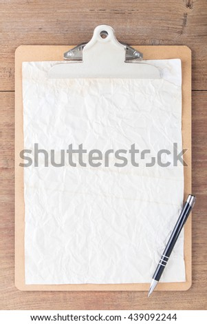 Vintage clipboard on a old wooden desk, with white blank paper. - stock photo