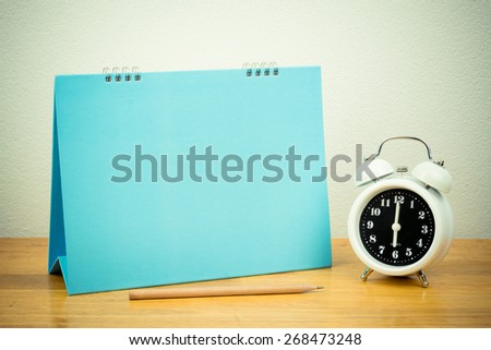vintage clock and blank paper with pencil, on wooden table.