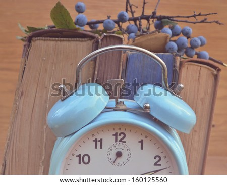 Vintage clock and books - stock photo