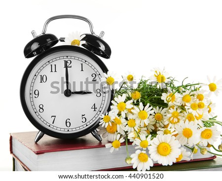 Vintage clock and bouquet of daisy flowers on pile of books on white background - stock photo