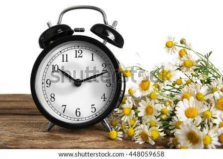 Vintage clock and bouquet of daisy flowers on wooden table - stock photo