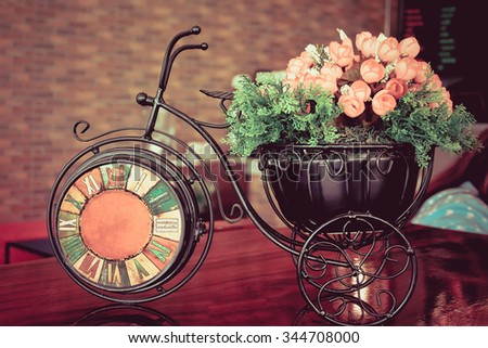 Vintage clock on wood table in coffee shop. Retro bicycle Clock with pink flowers plastic. - stock photo