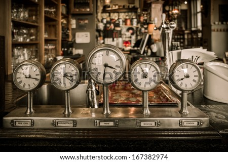 Vintage clocks on a bar counter in a pub - stock photo