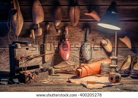 Vintage cobbler workshop with tools, shoes and laces - stock photo