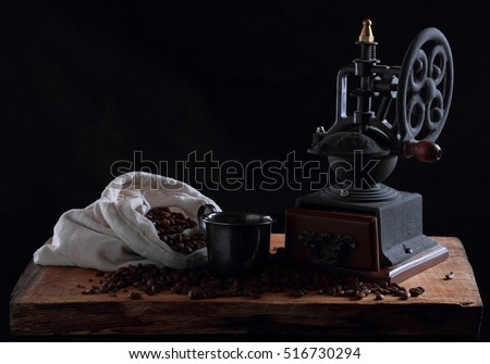 Vintage coffee grinder on a wooden desk. Black background