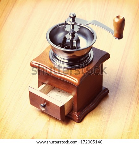 Vintage coffee grinder on wooden table - stock photo
