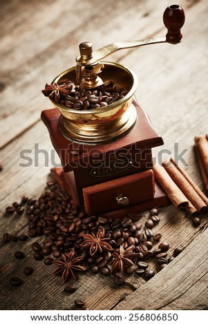 Vintage coffee grinder with coffee beans on wooden background - stock photo