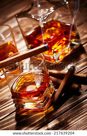 Vintage cognac with cigar over wooden background - stock photo