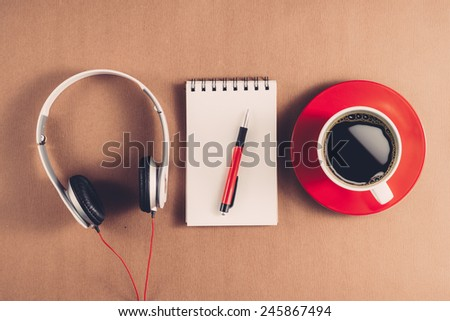 Vintage color. Closeup of white smartphone with black screen with headphones, sticky notes and bubbles on wooden surface. Square image format. Instant photo style retro filter. View from above - stock photo