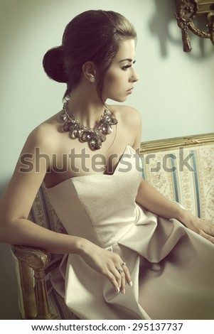 vintage color effect ,indoor portrait of aristocratic brunette girl sitting on vintage sofa with elegant pink dress, shiny necklace and classic hair-style. Luxury girl in ancient room