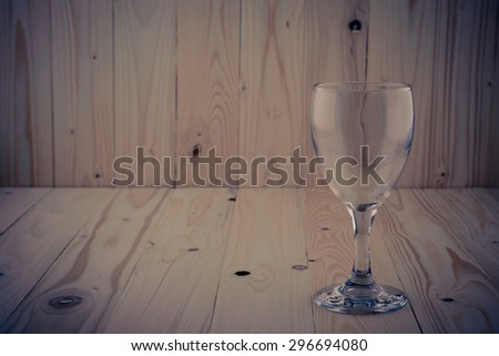 Vintage color Empty Glass of wine on the brown wooden background - stock photo