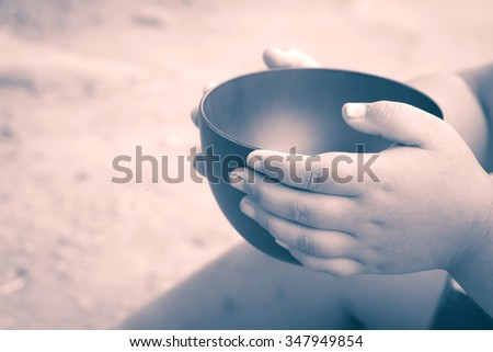 vintage color of a hungry children holding an empty bowl - stock photo