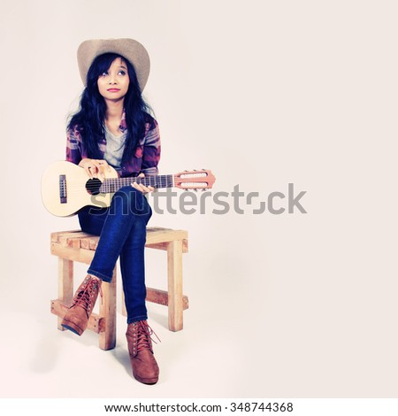 Vintage color portrait of country style girl posing with her small guitar on a chair - stock photo