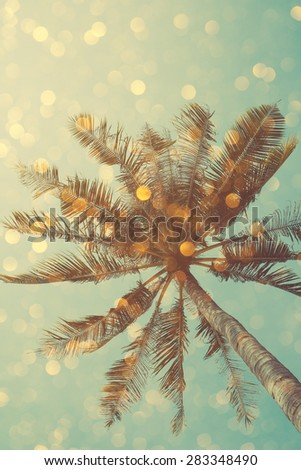 Vintage color stylized palm tree with bright party bokeh light overlay, double exposure effect - stock photo