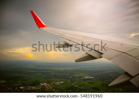Vintage color tone of Morning sunrise with Wing of an airplane. Photo applied to tourism operators. picture for add text message or frame website. Traveling concept