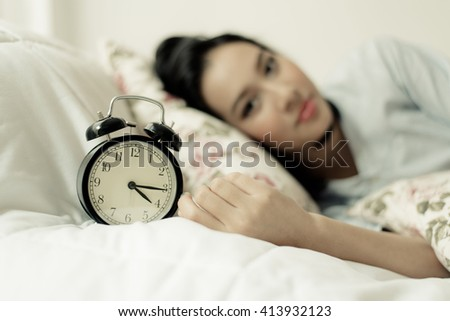 Vintage color tone. Selective focus on antique black alarm clock in front of young and beautiful asian girl on the bed.