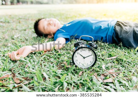 Vintage color tone, Selective focus on the classical black alarm clock model, in front of the sleeping young boy on green lawn in the park in day time. - stock photo