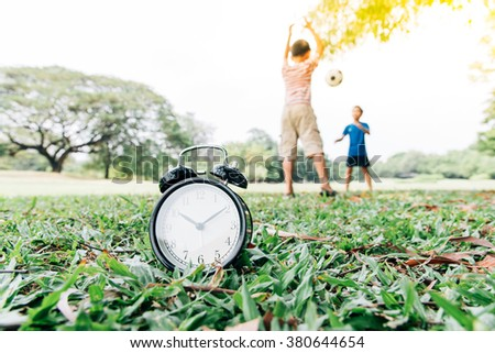Vintage color tone, Selective focus on the classical black alarm clock model, in front of the two young boy play football on green lawn, in the park in day time. - stock photo