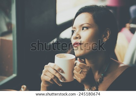 vintage color tone style of beauty girl with cup of coffee in coffee shop - stock photo