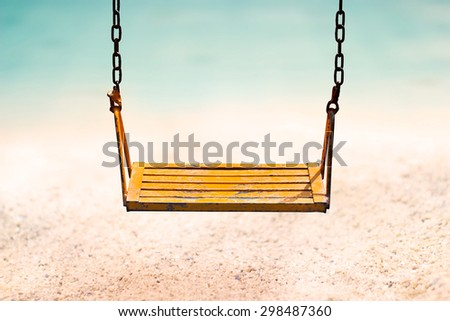 vintage color tone style of yellow swing on sand sea beach summer day - stock photo