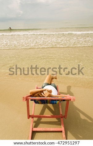 Vintage color warm tone. Woman lay on pink beach chair at the close of the sea water.