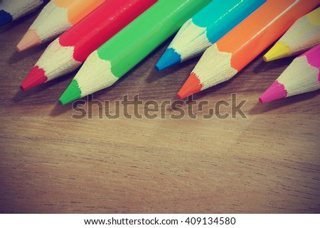 Vintage colored pencils on wooden background