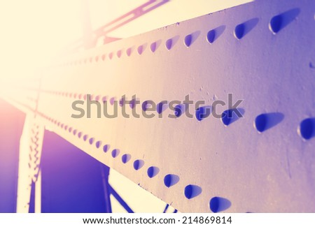 Vintage colorful abstract background of steel construction with rivets, shallow depth of field. - stock photo