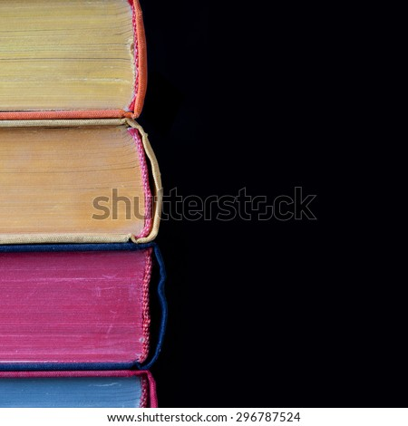 Vintage colorful books. Macro view, page texture, hard cover. Black background. Copy space.