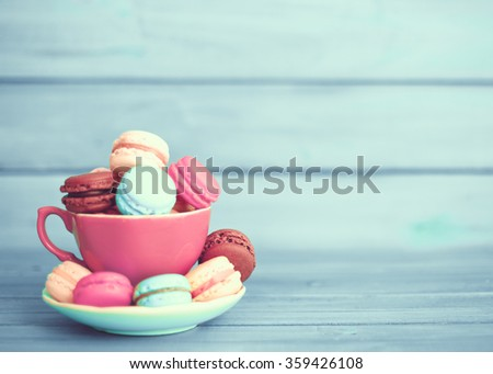 Vintage colorful macarons in a coffee cup over turquoise wood - stock photo