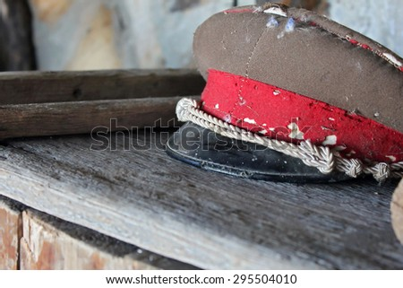 Vintage communism soldier's cap on wooden table  - stock photo