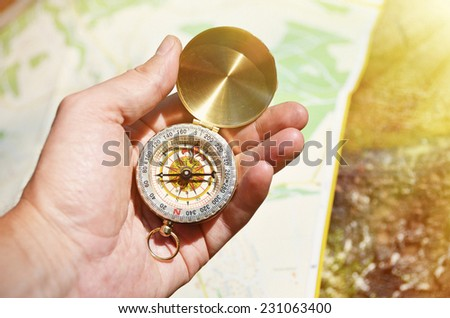 Vintage compass in the hand against a map - stock photo