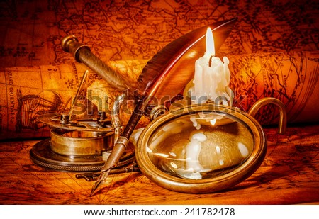 Vintage compass, magnifying glass, pocket watch, quill pen, spyglass lie on an old ancient map in 1565 with a lit candle. Vintage still life. - stock photo