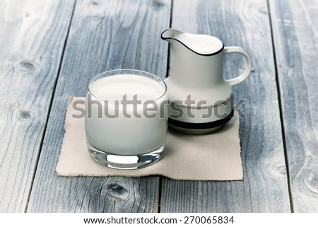 Vintage concept of a  glass of milk and pitcher on rustic wood   - stock photo