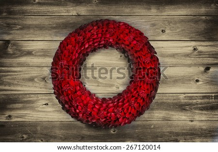 Vintage concept of a wooden petal red holiday wreath on rustic wood  - stock photo