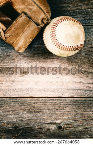 Vintage concept of an old baseball and weathered leather mitt on rustic wood. Format in vertical layout.  - stock photo