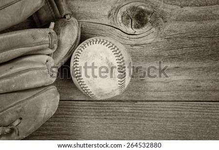 Vintage concept of old baseball and mitt on rustic wood. Layout in horizontal format. Slight vignette on border.  - stock photo