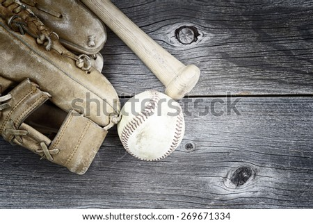 Vintage concept of  old worn glove, bat and used baseball on rustic wood  - stock photo
