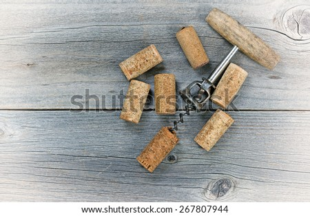 Vintage concept of several used wine corks and opener on rustic wooden boards.  - stock photo