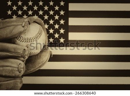 vintage concept of worn leather mitt and used baseball with United States of America flag in background.  - stock photo