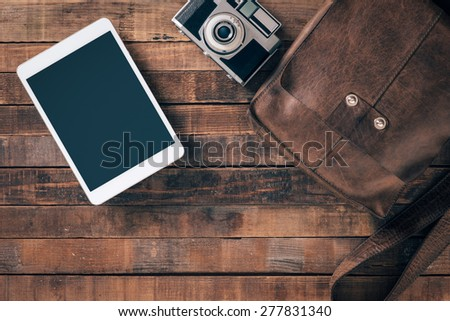 Vintage contemporary traveler and tourist equipment on a table, leather bag, camera and digital tablet, top view - stock photo