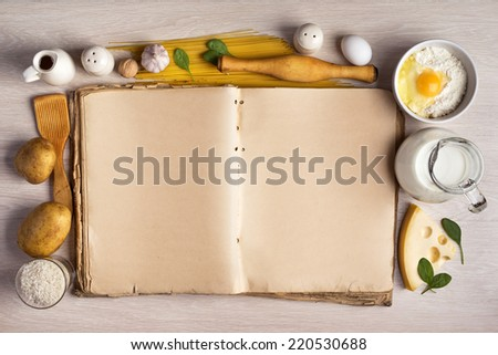 vintage cook book and ingredients for the food recipe around in a frame on the background of the table - stock photo
