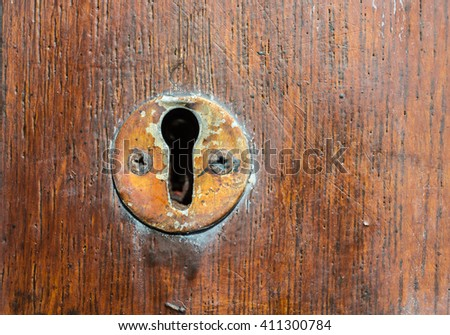 Vintage copper keyhole on old wooden door background - stock photo