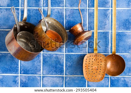 Vintage copper utensils. cookware, kitchenware set. Pots, coffee maker, kitchen spoon, skimmer hanging on.  Blue tile wall background. - stock photo
