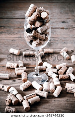 vintage cork from wine bottle and glass on the wood floor - stock photo