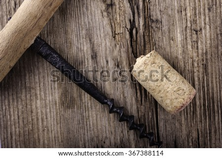 vintage corkscrew and wine cork on wooden surface macro closeup - stock photo