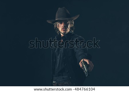 Vintage cowboy shooting with gun. Young man. Studio shot against dark wall.