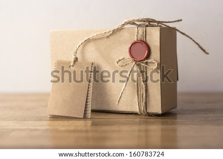 Vintage craft cardboard gift box with red seal on wooden table - stock photo